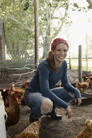 Portrait smiling female farmer with chickens in chicken coop 11096056134| 写真素材・ストックフォト・画像・イラスト素材|アマナイメージズ