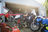 Mother and daughter fixing motorbike in sunny driveway 11096056954| 写真素材・ストックフォト・画像・イラスト素材|アマナイメージズ