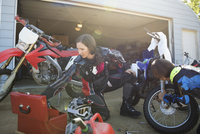 Mother and daughter fixing motorbike in sunny driveway 11096056955| 写真素材・ストックフォト・画像・イラスト素材|アマナイメージズ