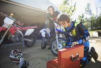 Mother and daughter fixing motorbike in sunny driveway 11096056956| 写真素材・ストックフォト・画像・イラスト素材|アマナイメージズ