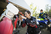 Mother and daughter fixing motorbike in driveway 11096056957| 写真素材・ストックフォト・画像・イラスト素材|アマナイメージズ