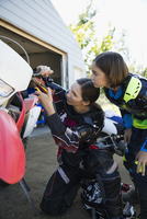 Mother and daughter fixing motorbike in driveway 11096056959| 写真素材・ストックフォト・画像・イラスト素材|アマナイメージズ