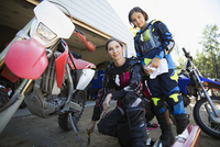 Portrait confident mother and daughter fixing motorbike in driveway 11096056963| 写真素材・ストックフォト・画像・イラスト素材|アマナイメージズ