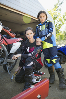 Portrait confident mother and daughter fixing motorbike in driveway 11096056964| 写真素材・ストックフォト・画像・イラスト素材|アマナイメージズ