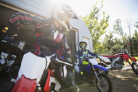 Mother and daughter on motorbikes in sunny driveway 11096056972| 写真素材・ストックフォト・画像・イラスト素材|アマナイメージズ