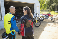 Affectionate couple holding hands near motorbikes in sunny driveway 11096056978| 写真素材・ストックフォト・画像・イラスト素材|アマナイメージズ