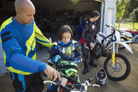 Father helping daughter on motorbike in driveway 11096056981| 写真素材・ストックフォト・画像・イラスト素材|アマナイメージズ