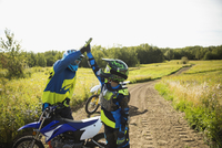 Father and daughter high-fiving at motorbike on sunny rural dirt road 11096056989| 写真素材・ストックフォト・画像・イラスト素材|アマナイメージズ