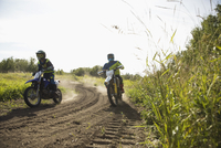 Father and daughter riding motorbikes on rural dirt road 11096056990| 写真素材・ストックフォト・画像・イラスト素材|アマナイメージズ