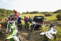 Men with motorbikes putting on jackets at trucks in rural field 11096057004| 写真素材・ストックフォト・画像・イラスト素材|アマナイメージズ