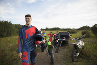 Portrait confident young man with motorbike in rural field 11096057008| 写真素材・ストックフォト・画像・イラスト素材|アマナイメージズ
