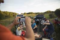 Man with camera phone photographing friends drinking beers at campfire near motorbikes in rural field 11096057052| 写真素材・ストックフォト・画像・イラスト素材|アマナイメージズ