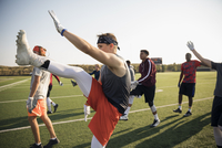 Teenage boy high school football team practicing leg kick drills on sunny football field 11096057238| 写真素材・ストックフォト・画像・イラスト素材|アマナイメージズ
