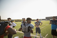 Teenage boy high school football team putting on padding for practice on sunny football field 11096057247| 写真素材・ストックフォト・画像・イラスト素材|アマナイメージズ