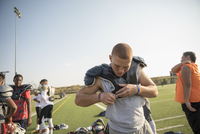 Teenage boy high school football player putting on padding for practice on sunny football field 11096057248| 写真素材・ストックフォト・画像・イラスト素材|アマナイメージズ