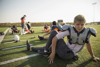 Teenage boy high school football player in padding stretching on sunny football field 11096057252| 写真素材・ストックフォト・画像・イラスト素材|アマナイメージズ