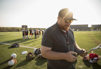 High school football coach reviewing game plan on clipboard on sunny football field 11096057254| 写真素材・ストックフォト・画像・イラスト素材|アマナイメージズ