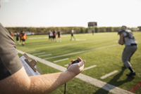Coach with stopwatch timing teenage boy high school football team running drills on sunny football field 11096057256| 写真素材・ストックフォト・画像・イラスト素材|アマナイメージズ