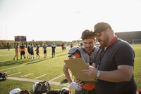 Coach and teenage boy high school football player reviewing game plan on clipboard on sunny football field 11096057261| 写真素材・ストックフォト・画像・イラスト素材|アマナイメージズ