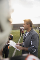 Coach with clipboard talking to teenage boy high school football team on football field 11096057262| 写真素材・ストックフォト・画像・イラスト素材|アマナイメージズ
