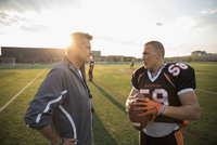 Coach and teenage boy high school football player talking on football field at sunset 11096057264| 写真素材・ストックフォト・画像・イラスト素材|アマナイメージズ