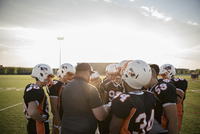 Coach and teenage boy high school football team talking in huddle on sunny football field 11096057267| 写真素材・ストックフォト・画像・イラスト素材|アマナイメージズ