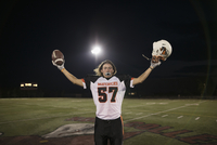 Portrait confident teenage boy high school football player cheering on football field 11096057274| 写真素材・ストックフォト・画像・イラスト素材|アマナイメージズ