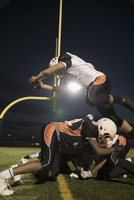 Teenage boy high school football player running back jumping over competitor to score on football field 11096057348| 写真素材・ストックフォト・画像・イラスト素材|アマナイメージズ