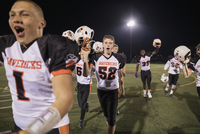 Teenage boy high school football team cheering, celebrating and holding helmets on football field 11096057358| 写真素材・ストックフォト・画像・イラスト素材|アマナイメージズ