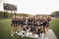 Portrait confident teenage high school cheerleading team and football players  on football field 11096057406| 写真素材・ストックフォト・画像・イラスト素材|アマナイメージズ