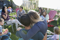 Affectionate couple hugging, enjoying backyard barbecue with neighbors and family 11096057793| 写真素材・ストックフォト・画像・イラスト素材|アマナイメージズ