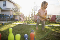 Cute toddler girl playing with bowling toy in grass in sunny backyard 11096057948| 写真素材・ストックフォト・画像・イラスト素材|アマナイメージズ