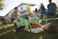 Brother in dinosaur costume tackling, playing with sister in backyard 11096057954| 写真素材・ストックフォト・画像・イラスト素材|アマナイメージズ