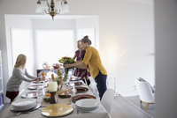 Grandmother and granddaughters arranging flowers and setting the table for Thanksgiving dinner 11096058006| 写真素材・ストックフォト・画像・イラスト素材|アマナイメージズ