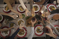 Overhead view family toasting wine glasses at candlelight Christmas turkey  dinner at table 11096058126| 写真素材・ストックフォト・画像・イラスト素材|アマナイメージズ