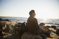 Serene man with hiking backpack relaxing, sitting on sunny ocean beach 11096058456| 写真素材・ストックフォト・画像・イラスト素材|アマナイメージズ