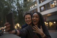 Young couple with camera phone taking selfie with engagement ring on urban night sidewalk 11096058595| 写真素材・ストックフォト・画像・イラスト素材|アマナイメージズ