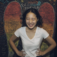 Portrait enthusiastic, laughing Korean tween girl against wall with chalk wings