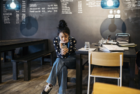 Asian tween girl texting with smart phone at cafe table 11096059014| 写真素材・ストックフォト・画像・イラスト素材|アマナイメージズ