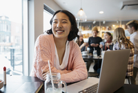Smiling, confident Korean high school girl student studying at laptop in cafe 11096059121| 写真素材・ストックフォト・画像・イラスト素材|アマナイメージズ