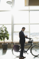 Businessman commuter with bicycle texting with smart phone in sunny office lobby 11096059407| 写真素材・ストックフォト・画像・イラスト素材|アマナイメージズ