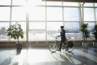 Businessman commuter in helmet walking bicycle in sunny office lobby 11096059408| 写真素材・ストックフォト・画像・イラスト素材|アマナイメージズ