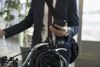 Close up businessman commuter with bicycle texting with smart phone 11096059409| 写真素材・ストックフォト・画像・イラスト素材|アマナイメージズ