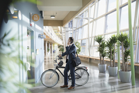 Businessman commuter with bicycle talking on smart phone, waiting at elevator in office lobby 11096059410| 写真素材・ストックフォト・画像・イラスト素材|アマナイメージズ
