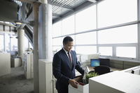 Businessman being laid off, holding box of belongings at office cubicle