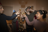 Festive millennial friends celebrating New Years Eve, toasting champagne flutes