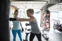 Young women friends boxing at punching bag in garage