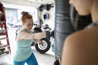 Focused woman boxing at punching bag in garage