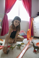 Girl playing with toy car track and dinosaurs in bedroom 11096064936| 写真素材・ストックフォト・画像・イラスト素材|アマナイメージズ