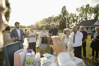 Man with camera phone photographing senior bride and groom cutting wedding cake in rural garden 11096065320| 写真素材・ストックフォト・画像・イラスト素材|アマナイメージズ